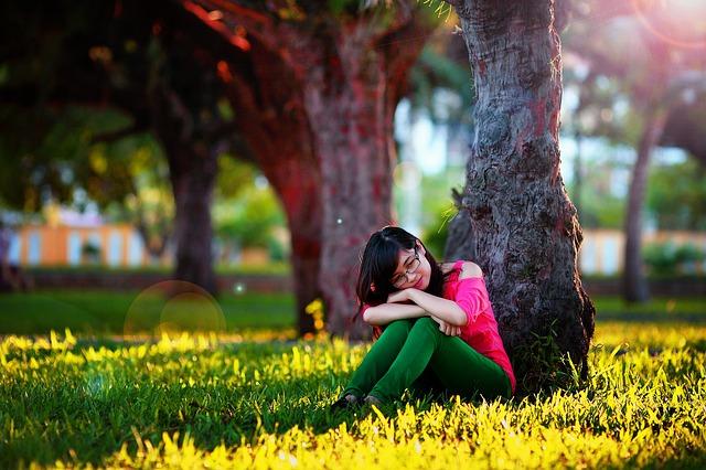 dívka sedí u stromu